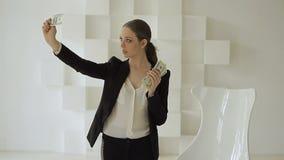 Όμορφη επιχειρηματίας στο επίσημο κοστούμι που εξιστορεί το σωρό των δολαρίων φιλμ μικρού μήκους