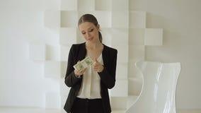 Όμορφη επιχειρηματίας στο επίσημο κοστούμι που εξιστορεί το σωρό των δολαρίων απόθεμα βίντεο
