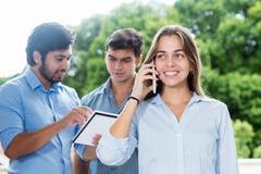 Όμορφη επιχειρηματίας στο τηλέφωνο με άλλο businesspeople Στοκ φωτογραφία με δικαίωμα ελεύθερης χρήσης