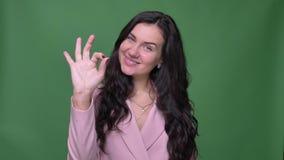 Όμορφη επιχειρηματίας brunette στο ρόδινο σακάκι που το εντάξει σημάδι στη κάμερα στο πράσινο υπόβαθρο απόθεμα βίντεο
