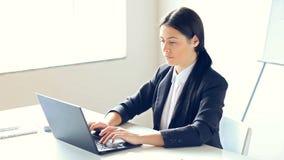 Όμορφη επιχειρησιακή γυναίκα που εργάζεται στο lap-top στο γραφείο φιλμ μικρού μήκους