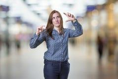 Όμορφη επιχειρησιακή γυναίκα που κάνει το μικροσκοπικό και μεγάλο σημάδι πέρα από το υπόβαθρο θαμπάδων Στοκ φωτογραφία με δικαίωμα ελεύθερης χρήσης