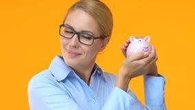 Όμορφη επιχειρησιακή γυναίκα που τινάζει τη piggy τράπεζα, ευνοϊκοί όροι πιστώσεων, χαμηλό ενδιαφέρον φιλμ μικρού μήκους