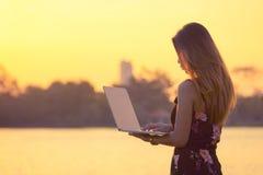 Όμορφη επιχειρησιακή γυναίκα που χρησιμοποιεί το lap-top στο πάρκο κατά τη διάρκεια του ηλιοβασιλέματος στοκ εικόνες