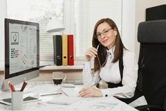 Όμορφη επιχειρησιακή γυναίκα στο κοστούμι και γυαλιά που λειτουργούν στον υπολογιστή με τα έγγραφα στο ελαφρύ γραφείο στοκ εικόνα με δικαίωμα ελεύθερης χρήσης