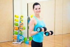 Όμορφη λεπτή γυναίκα με τους αλτήρες στη γυμναστική Στοκ Εικόνα