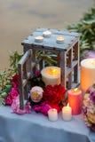 Όμορφη, λεπτή νυφική ανθοδέσμη μεταξύ της διακόσμησης με τα κεριά και τα φρέσκα λουλούδια Στοκ Εικόνες