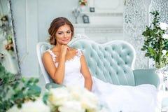 Όμορφη, ευγενής νύφη στο άσπρο γαμήλιο φόρεμα στο δωμάτιο πολυτέλειας Στοκ Εικόνες