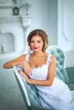 Όμορφη, ευγενής νύφη στο άσπρο γαμήλιο φόρεμα στο δωμάτιο πολυτέλειας Στοκ Φωτογραφίες