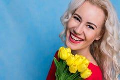 Όμορφη Ευρωπαία γυναίκα με μια ανθοδέσμη των τουλιπών ενάντια στις λευκές κίτρινες νεολαίες άνοιξη λουλουδιών έννοιας ανασκόπησης Στοκ φωτογραφία με δικαίωμα ελεύθερης χρήσης