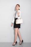 Όμορφη ευτυχής ασιατική γυναίκα που κρατά μια τσάντα περπατώντας πέρα από την γκρίζα πλάτη Στοκ Εικόνα