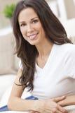 όμορφη ευτυχής γυναίκα καναπέδων συνεδρίασης χαμογελώντας στοκ φωτογραφία με δικαίωμα ελεύθερης χρήσης