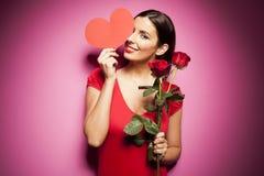 Όμορφη ευτυχής γυναίκα με το μπαλόνι ημέρας βαλεντίνων στο ρόδινο υπόβαθρο στοκ εικόνες
