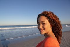 Όμορφη ευτυχής γυναίκα που εξετάζει τη κάμερα στην παραλία στην ηλιοφάνεια στοκ εικόνες με δικαίωμα ελεύθερης χρήσης