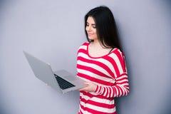 Όμορφη ευτυχής γυναίκα που στέκεται με το lap-top Στοκ φωτογραφίες με δικαίωμα ελεύθερης χρήσης