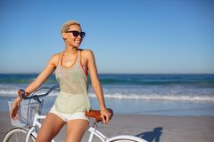 Όμορφη ευτυχής γυναίκα στα γυαλιά ηλίου που κάθεται στο ποδήλατο στην παραλία στην ηλιοφάνεια στοκ φωτογραφία