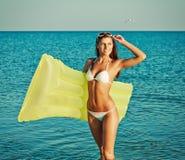 Όμορφη ευτυχής γυναίκα στο άσπρο μπικίνι με το κίτρινο διογκώσιμο στρώμα στην παραλία στοκ φωτογραφίες