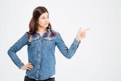 Όμορφη ευτυχής γυναίκα στο πουκάμισο τζιν που κοιτάζει και που δείχνει μακριά στοκ φωτογραφίες