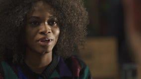 Όμορφη ευτυχής νέα αφρικανική γυναίκα στη καφετερία που μιλά και που πίνει συναισθηματικά τον καφέ κοντά επάνω φιλμ μικρού μήκους