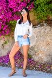 Όμορφη ευτυχής νέα γυναίκα μόδας που στέκεται σε ένα ζωηρόχρωμο φυσικό υπόβαθρο των φωτεινών ρόδινων λουλουδιών στοκ εικόνες με δικαίωμα ελεύθερης χρήσης