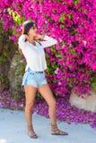 Όμορφη ευτυχής νέα γυναίκα μόδας που στέκεται σε ένα ζωηρόχρωμο φυσικό υπόβαθρο των φωτεινών ρόδινων λουλουδιών στοκ εικόνες