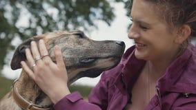 Όμορφη ευτυχής νέα γυναίκα που κτυπά την αγάπη & το πιστό σκυλί της Pet της στο πάρκο απόθεμα βίντεο