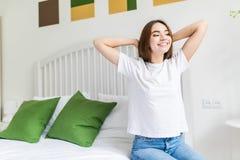 Όμορφη ευτυχής νέα γυναίκα που ξυπνά το πρωί και που τεντώνει στο κρεβάτι στο σπίτι με το χαμόγελο στοκ φωτογραφία με δικαίωμα ελεύθερης χρήσης