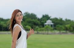Όμορφη ευτυχής νέα γυναίκα σε ένα πάρκο στοκ φωτογραφίες
