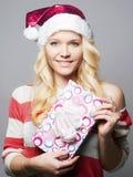 Όμορφη ευτυχής νέα γυναίκα στο καπέλο Άγιου Βασίλη στοκ φωτογραφία με δικαίωμα ελεύθερης χρήσης