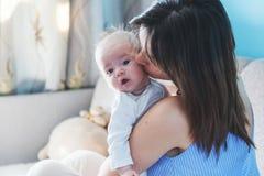 Όμορφη ευτυχής νέα γυναίκα brunette που κοσμεί το νεογέννητο μωρό της μέσα Στοκ Εικόνες