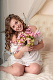 Όμορφη ευτυχής νέα ξανθή γυναίκα με μια ανθοδέσμη των λουλουδιών στην κρεβατοκάμαρα στοκ φωτογραφίες