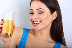 Όμορφη ευτυχής νέα υγιής περιστασιακή γυναίκα που πίνει το χυμό από πορτοκάλι Στοκ Εικόνα