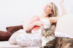 Όμορφη ευτυχής νέα χαλάρωση γυναικών με τις ιδιαίτερες προσοχές σε έναν καναπέ στοκ εικόνες με δικαίωμα ελεύθερης χρήσης