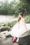 Όμορφη ευτυχής νύφη υπαίθρια σε ένα δάσος με τους βράχους Γαμήλια τέλεια ημέρα Στοκ Εικόνες