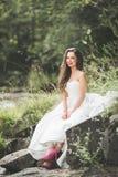 Όμορφη ευτυχής νύφη υπαίθρια σε ένα δάσος με τους βράχους Γαμήλια τέλεια ημέρα Στοκ Φωτογραφία