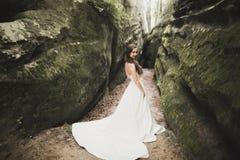 Όμορφη ευτυχής νύφη υπαίθρια σε ένα δάσος με τους βράχους Γαμήλια τέλεια ημέρα Στοκ Φωτογραφίες