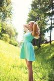 Όμορφη ευτυχής ξανθή γυναίκα στο φόρεμα στο ηλιόλουστο ελατήριο στοκ εικόνες με δικαίωμα ελεύθερης χρήσης