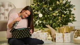 Όμορφη ευτυχής συνεδρίαση γυναικών δίπλα στο χριστουγεννιάτικο δέντρο με ένα δώρο στα χέρια της Χαρούμενα Χριστούγεννα και νέα έν απόθεμα βίντεο