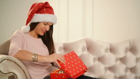 Όμορφη ευτυχής συνεδρίαση γυναικών δίπλα στο χριστουγεννιάτικο δέντρο με ένα δώρο στα χέρια της Χαρούμενα Χριστούγεννα και νέα έν φιλμ μικρού μήκους