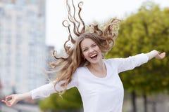Όμορφη ευτυχής χαμογελώντας γυναίκα με την τρίχα που πετά στο sity υπόβαθρο Στοκ εικόνα με δικαίωμα ελεύθερης χρήσης