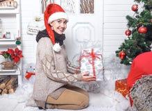 Όμορφη ευτυχής χαμογελώντας γυναίκα που φορά το καπέλο Santa ` s, που κάθεται πλησίον στοκ εικόνα