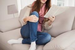 Όμορφη εφημερίδα ανάγνωσης brunette στον καναπέ Στοκ Φωτογραφία