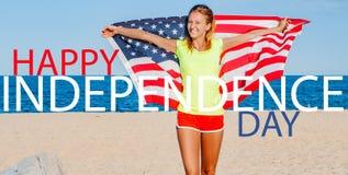 Όμορφη εύθυμη γυναίκα που κρατά μια αμερικανική σημαία στην παραλία στοκ εικόνες