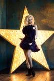 Όμορφη εύθυμη ενήλικη ξανθή γυναίκα που φορά το σκούρο μπλε tutu δαντελλών Στοκ εικόνες με δικαίωμα ελεύθερης χρήσης