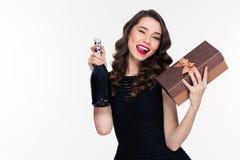 Όμορφη εύθυμη κλείνοντας το μάτι γυναίκα με το μπουκάλι της σαμπάνιας και του παρόντος Στοκ εικόνα με δικαίωμα ελεύθερης χρήσης