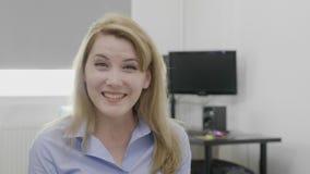 Όμορφη εύθυμη νέα επιχειρησιακή γυναίκα που έχει μια ευτυχή αντίδραση που εκπλήσσεται από τις μεγάλες ειδήσεις με το γραφείο - απόθεμα βίντεο