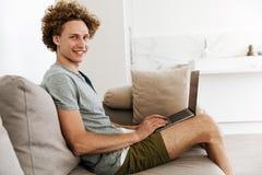 Όμορφη εύθυμη συνεδρίαση ατόμων στον καναπέ που χρησιμοποιεί το φορητό προσωπικό υπολογιστή Στοκ Εικόνα