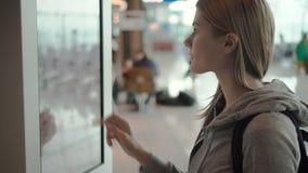 Όμορφη ελκυστική γυναίκα στο τερματικό αερολιμένων Διαταγή των τροφίμων μέσω της μηχανής αυτοεξυπηρετήσεων σε Mcdonald ` s απόθεμα βίντεο