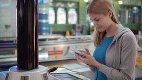 Όμορφη ελκυστική γυναίκα στο τερματικό αερολιμένων Στάση κοντά στη χρέωση στάσεων στο smartphone απόθεμα βίντεο