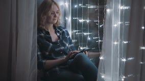 Όμορφη ελκυστική γυναίκα χρησιμοποιώντας το PC ταμπλετών και καθμένος σε Windowsill που διακοσμείται με τις γιρλάντες απόθεμα βίντεο
